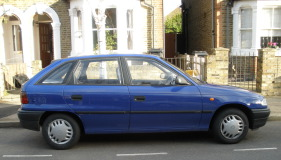 Blue Vauxhall Astra parked in front of semi-detached houses.