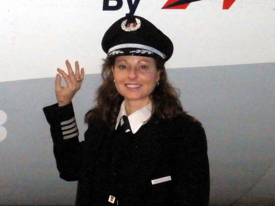 Closeup of Gina in her Captain's uniform standing next to a CRJ.